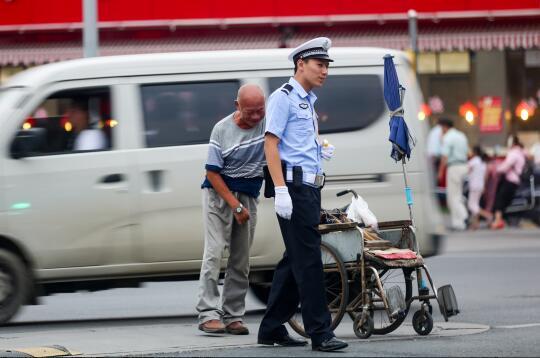 老人扶轮椅过马路被困道路中央 济南暖心交警开路护送