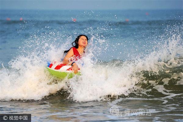 山东青岛:台风扫尾海上刮大风 游客冒险海面戏浪