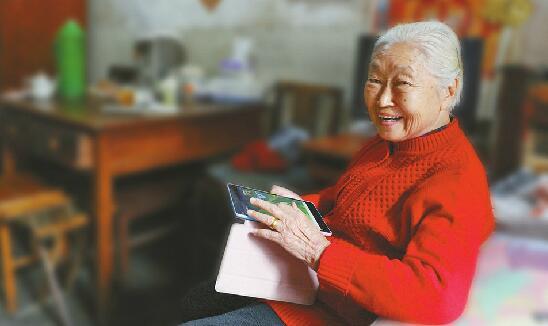 19日,90岁的薄淑兰在家中使用平板电脑。 记者王汗冰 摄   56岁的市民郇春莉向记者抱怨说,她学习用智能手机的过程简直比孩子中、高考还辛苦:巴掌大的屏幕看起来耗费眼力,时间一久头晕眼花;几十年前学的拼音早已放下,手写输入法经常提笔忘字;没有网银,不会绑定银行卡,眼看着微信红包就是抢不到。她拿起年轻时在工厂里争当红旗手的劲头,向身边的人不停询问,就为了能和身在北京的儿子每周电话报平安之外,还能通过网络与他隔空联系。她还为此专门上了社区里的智能手机学习班,一进教室,好嘛!