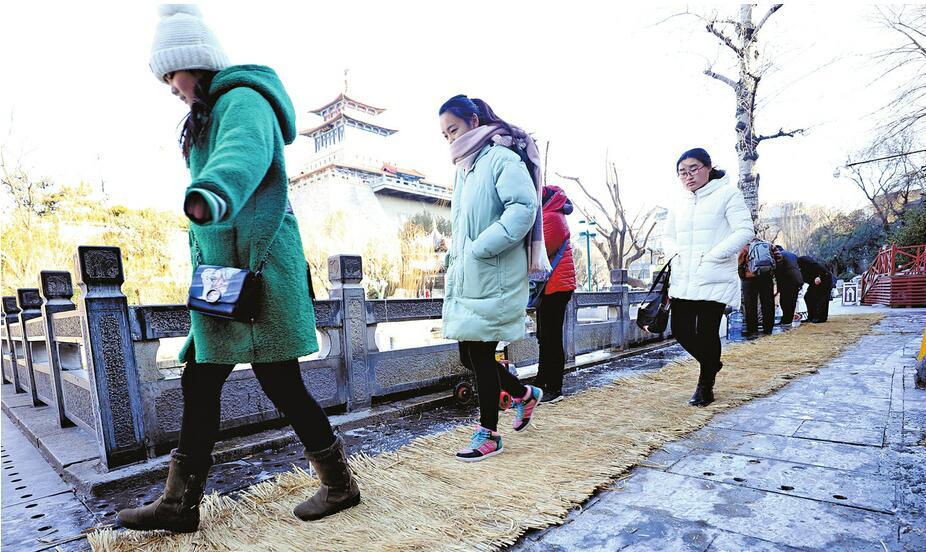 济南市区气温走低 黑虎泉边取水有了草垫防滑通道