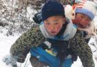 9岁半的凉山男孩雪中背1岁半的弟弟 200米落差山路走50分钟