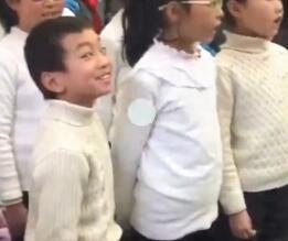 """近日,某学校里学生大合唱,站在边上的一个小男孩成功抢镜。只见这个小男孩双手插在裤兜里,表情丰富、极为卖力地和大家一起唱着校歌,用情至深甚至一度唱到翻白眼。在发现自己被拍摄后,表演欲更是爆发,跟着节奏摇头晃脑,还不忘对着镜头挑眉毛、抛媚眼。网友们纷纷评论:""""这是戏精本精""""、""""不愧是灵魂歌手""""、""""不靠C位靠演技""""!"""
