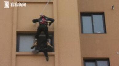 """赞叹!消防队员索降救人 从8楼""""闪电索降""""将该女子推进楼内"""