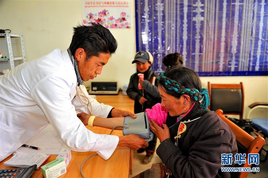 普玛江塘乡卫生院全科医生旺扎为农牧民查体。2014年,旺扎从西藏藏医学院毕业,来到条件艰苦的乡卫生院工作,承担全乡282户近1100人的卫生保健任务。
