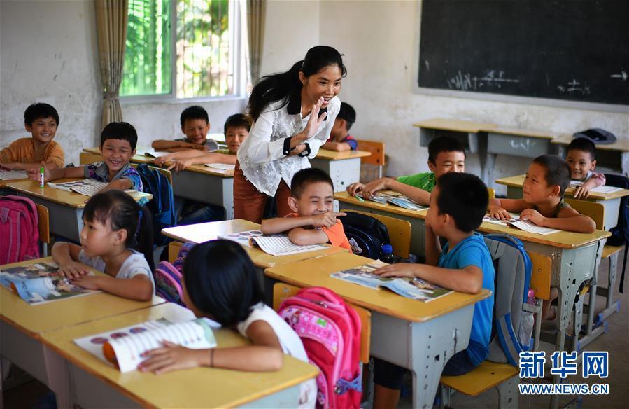 特岗乡村英语教师黄妮娜(中)在海南省保亭黎族苗族自治县保城镇西坡小学上课。她分管三个小学,每周要上27节课。