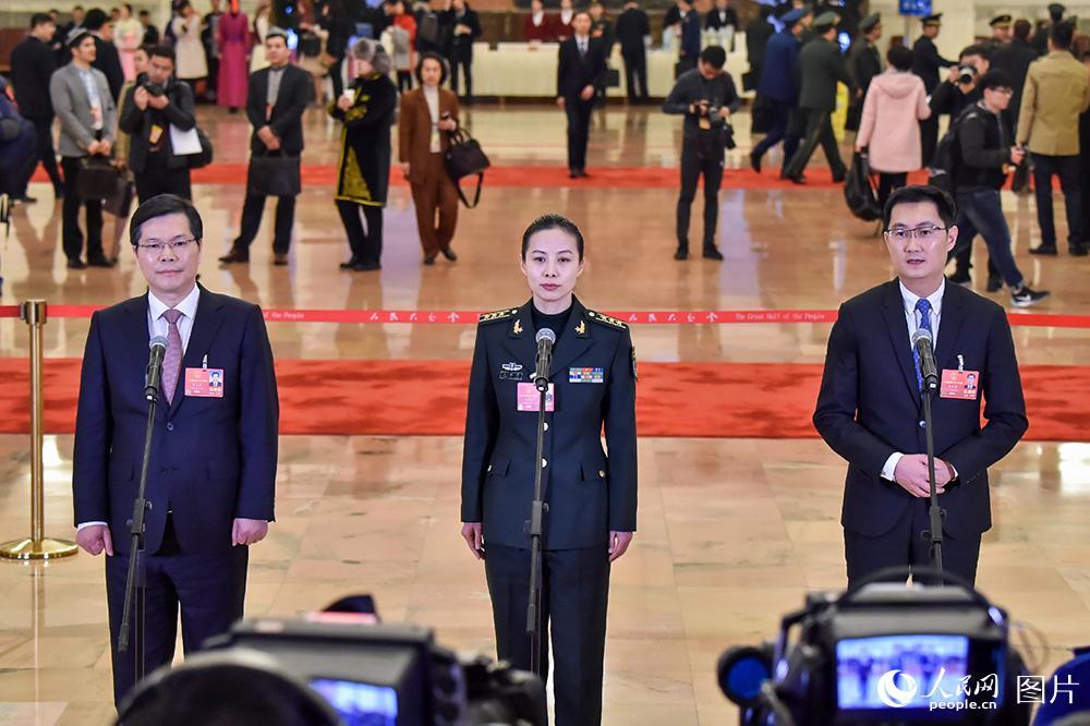 """3月5日,第十三届全国人民代表大会第一次会议在北京人民大会堂开幕。根据大会安排,首场""""代表通道""""集中采访活动在人民大会堂中央大厅北侧进行,10名全国人大代表接受采访。"""