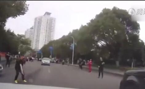 哭笑不得!横跨马路打羽毛球太惊险 汽车从球下穿行