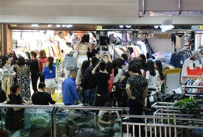 凌晨4点的九龙广场,穿版模特将新到的衣服穿上身,进货商家高举手臂表示要购买这个款式