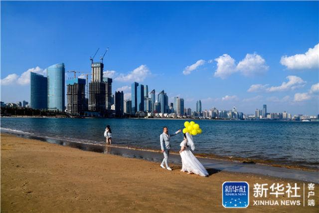 ↑新人们在青岛第三海水浴场拍摄婚纱照(5月4日摄)。新华社记者 郭绪雷 摄