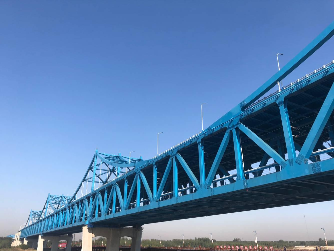 """跨越黄河牵手东站 作为本次联调联试的枢纽部位——石济高铁跨黄河特大桥,该桥由中铁四局承建,全长14.032km,向南接入济南新东站,其中主桥石济高铁黄河公铁两用桥横跨黄河两岸,是我国首例大跨度刚性悬索加劲连续钢桁梁公铁两用桥,素有""""桥梁工法博物馆""""之称。该桥作为石济铁路客运专线工程、邯济铁路至胶济铁路联络线工程和济南市""""北跨""""城市空间发展跨越黄河通道的公铁合建桥梁,三项工程融为一体,主桥全长1."""