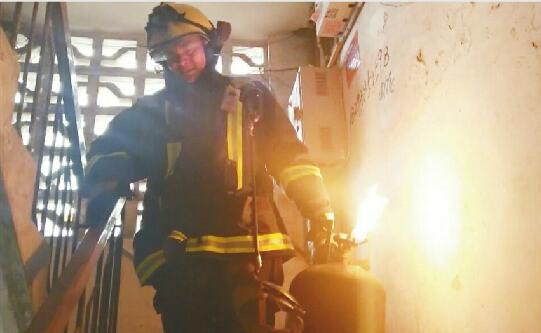 """二楼拎下喷火煤气罐 消防员""""抱火哥""""只用30秒"""