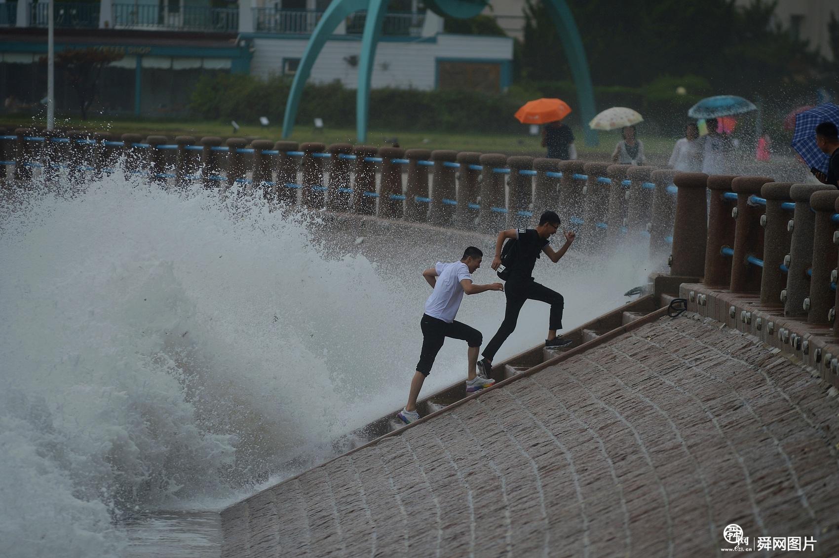 受台风影响青岛沿海现大潮,游客冒险观潮戏浪